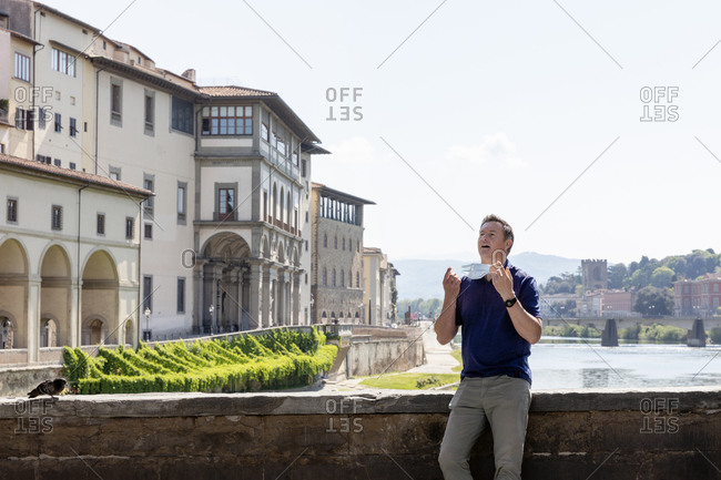 Man holding face mask standing alone on bridge over River Arno in Florence, Italy during the Corona virus crisis.