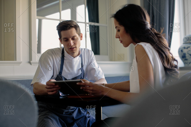 Chef wearing blue apron and woman sitting at a table, looking at digital tablet.