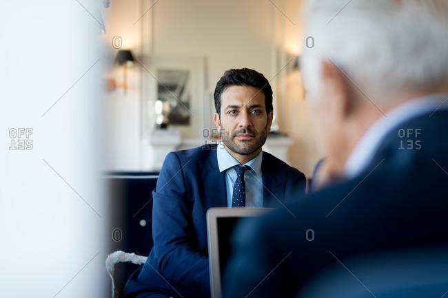 Two businessmen sitting indoors, talking.