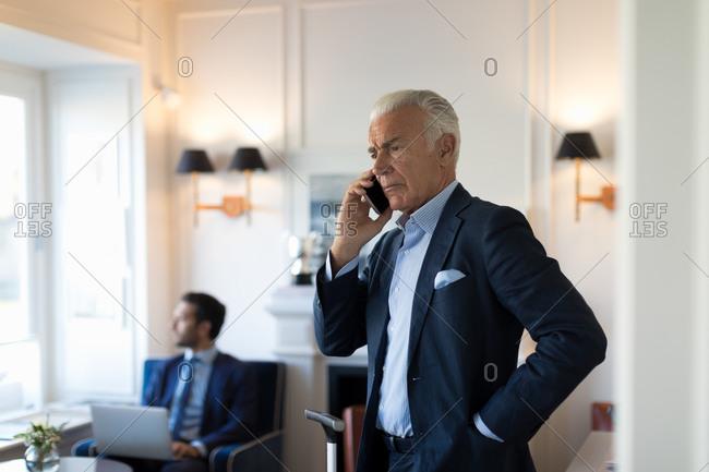 Senior businessman standing indoors, using mobile phone.