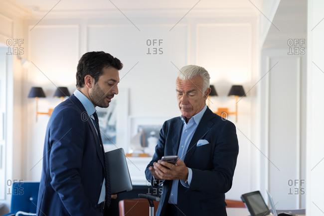 Two businessmen standing indoors, talking.