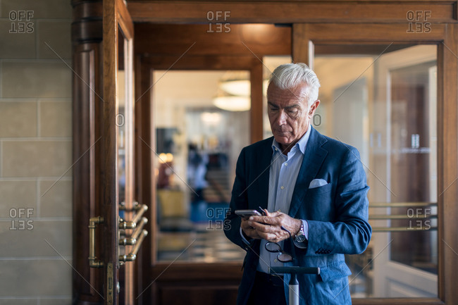 Senior businessman standing in hotel lobby, looking at mobile phone.