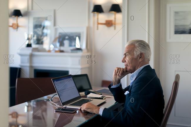 Senior businessman sitting at desk, looking at laptop.