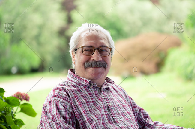 Portrait of senior man with moustache wearing glasses sitting in garden, smiling at camera.