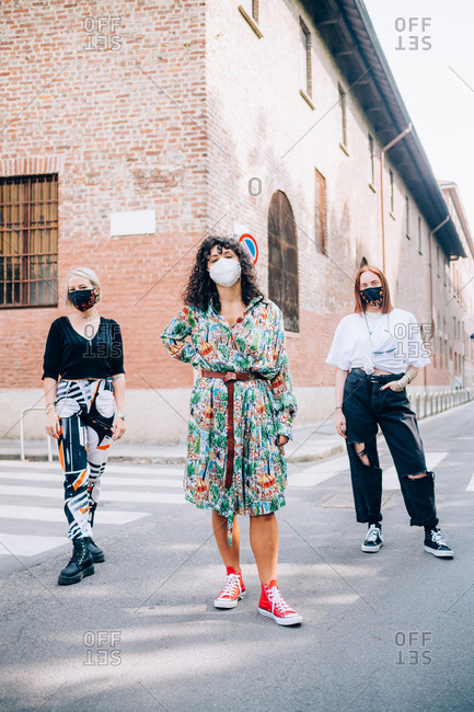 Three young women wearing face masks during Corona virus, standing on a pedestrian crossing in a street.