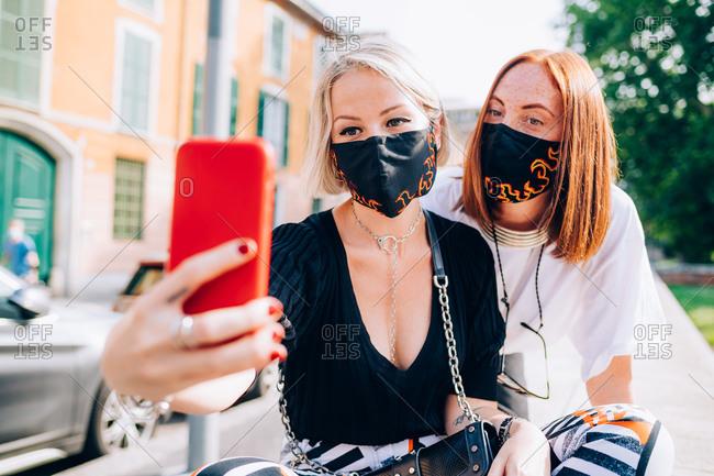 Two young women wearing face masks during Corona virus, sitting on a riverbank, taking selfie.