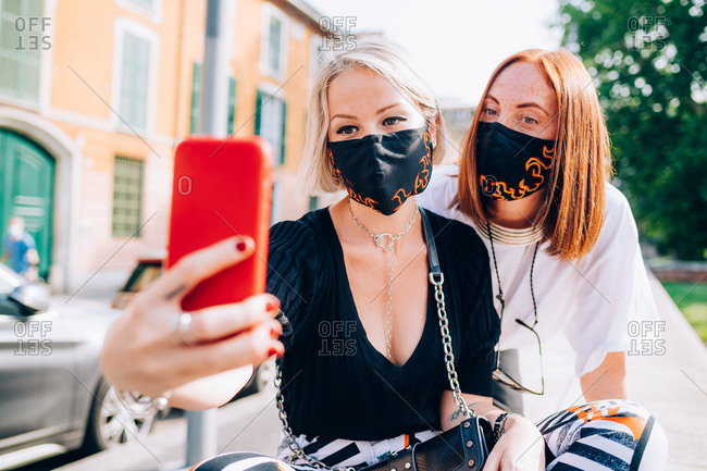 Two young women wearing face masks during Corona virus, sitting on a riverbank, taking selfie.