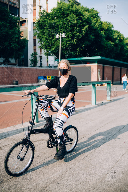 Young woman wearing face mask during Corona virus, cycling on folding bicycle.
