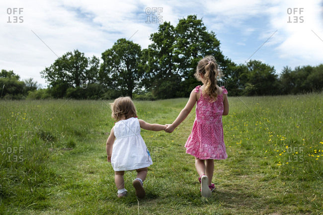 Rear view of two young girls walking hand in hand across a meadow.