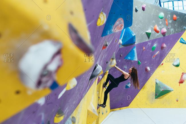Side view of woman ascending rock climbing wall.