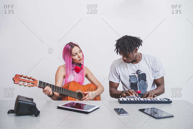 Young woman with long pink hair and young man with short dreadlocks playing guitar and keyboard.