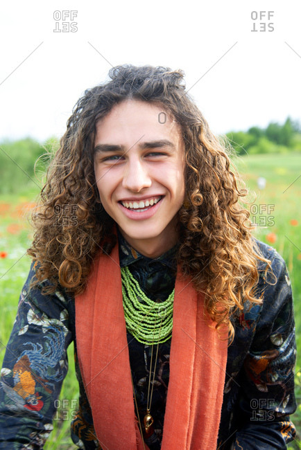 Portrait of young man with long brown curly hair in a poppy meadow, smiling at camera.