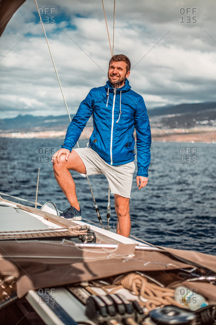 Portrait of smiling man standing aboard a sailing yacht.