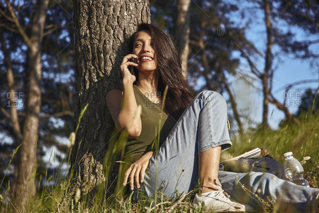 Portrait of young woman sitting under a tree in a forest, talking on mobile phone.