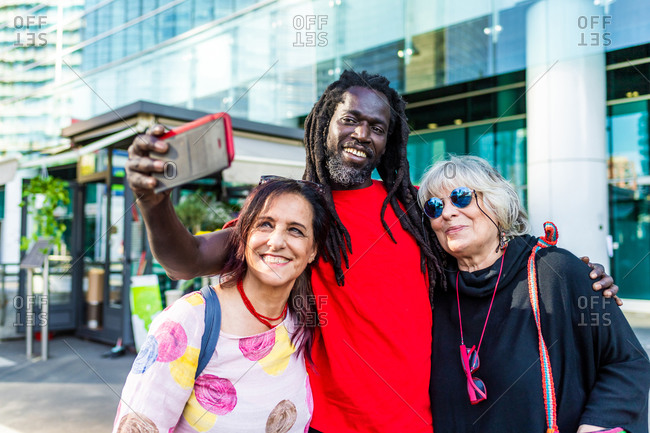 Black man with dreadlocks and two Caucasian women taking selfie with mobile phone.