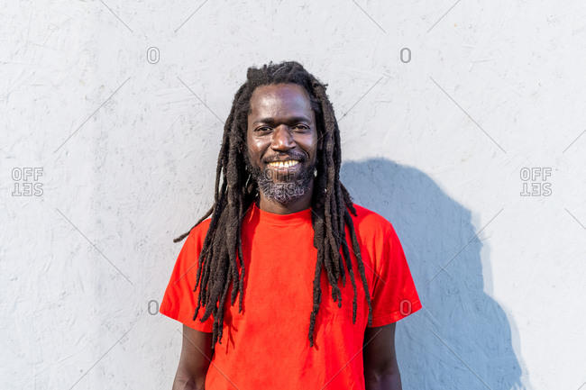 Portrait of Black man with dreadlocks wearing red T-Shirt, standing in front of white wall, smiling at camera.