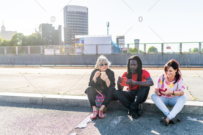 Black man with dreadlocks and two Caucasian women sitting on sidewalk, checking their mobile phones.