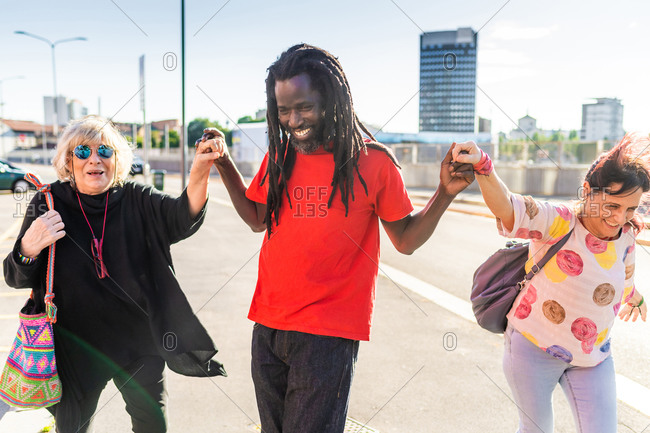 Black man with dreadlocks and two Caucasian women dancing in a street.