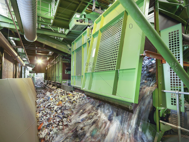 Mixed waste on conveyor belt in waste recycling plant.