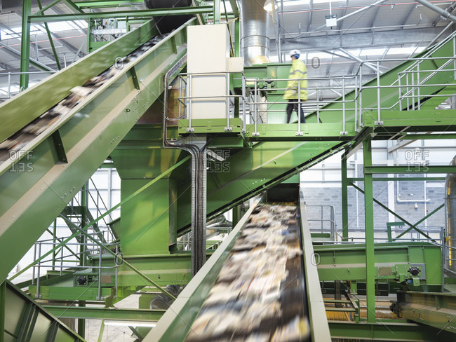 Worker checking conveyor belts with waste paper in waste recycling plant.