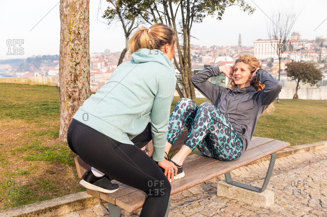 Two young women with long blond hair wearing sportswear, stretching on park bench after jogging.