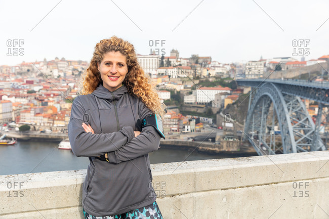 Portrait of young woman with long curly blond hair, wearing grey windbreaker, standing near Dom Luis I bridge in Porto, Portugal.