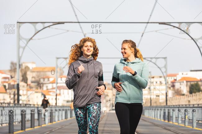 Two young women jogging on Dom Luis I bridge in Porto, Portugal.