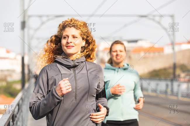 Two young women with long blond hair jogging on Dom Luis I bridge in Porto, Portugal.