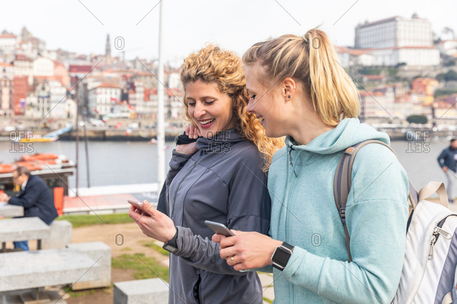 Two young women walking along river Douro, checking their phones, Porto, Portugal.