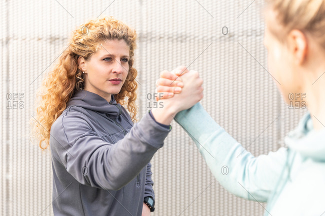 Two young women with long blond hair wearing sportswear, shaking hands after exercise.