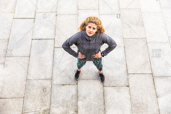 High angle portrait of young woman with long curly blond hair, wearing grey windbreaker.