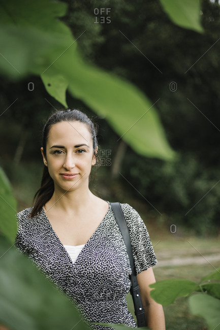 Portrait of smiling woman looking at camera standing on nature
