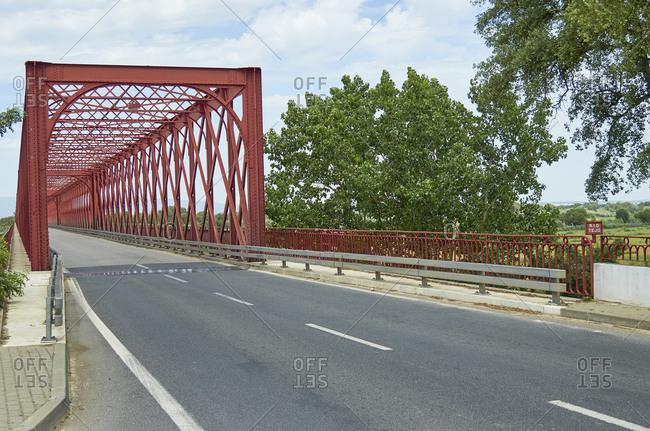 Red iron Ponte da Chamusca bridge near Golega, Portugal