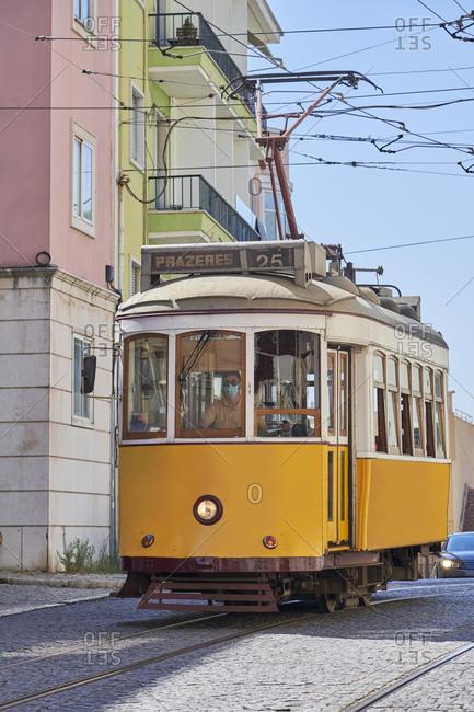 Tramway driving down cobblestone street in the Lapa neighborhood, Lisbon, Portugal