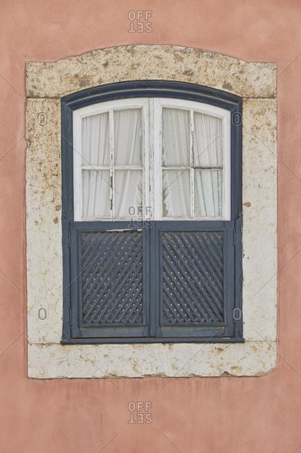 Window with gray shutters on pink home, Lapa neighborhood, Lisbon, Portugal