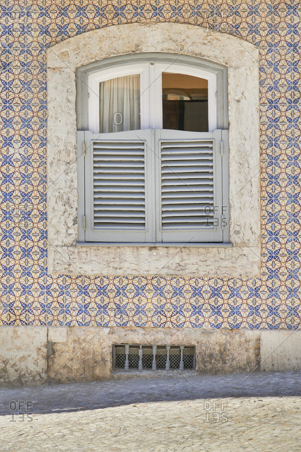 Home exterior with decorated tile around the window, Lapa neighborhood, Lisbon, Portugal