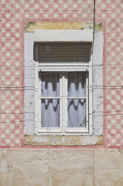 Home exterior with pink tile around window, Lapa neighborhood, Lisbon, Portugal