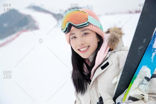 Beautiful young woman holding her skiis