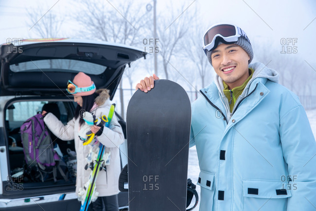 Young couple packing up car with ski equipment