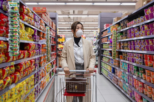 Young woman wearing a mask shopping in a supermarket