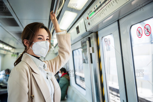Young woman wearing a mask taking the subway