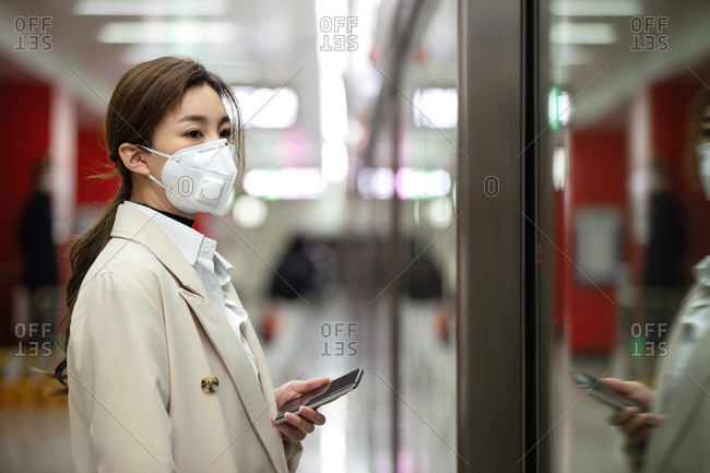 Young woman wearing a mask and standing on subway platform