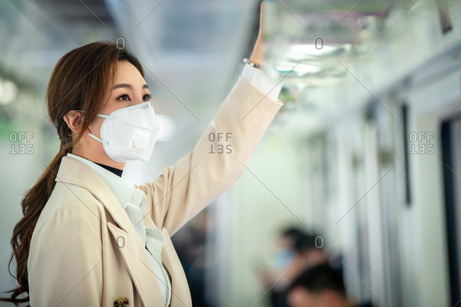 Young woman riding the subway,  wearing mask