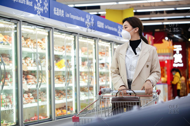 Young woman grocery shopping and wearing a mask