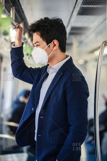 Young man wearing a mask taking the subway