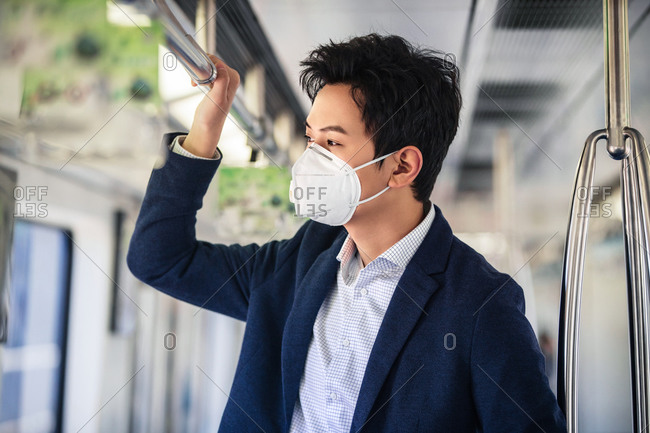 Young man taking the subway,  wearing a mask