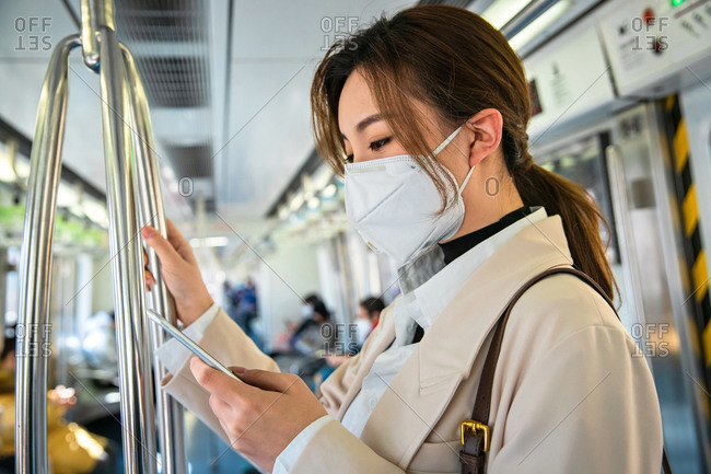 Young woman wearing a mask checking her phone on the train