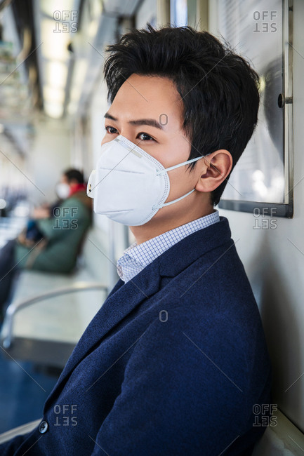 Young man wearing a mask sitting on the train
