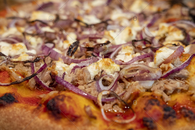 Pizza with red onion, feta cheese and tuna