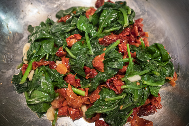 Spinach and sun-dried tomatoes in a pan